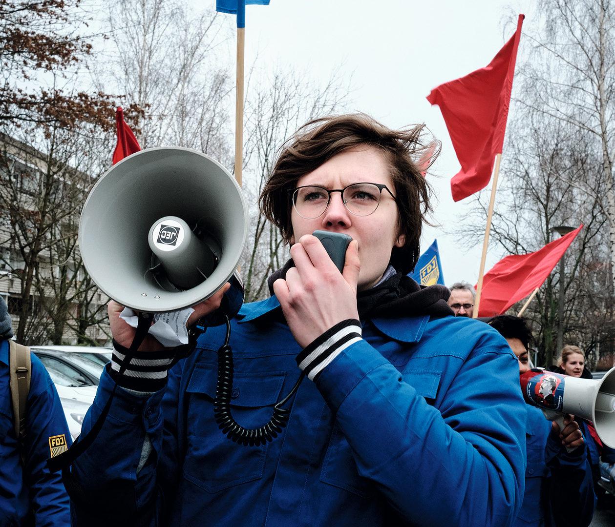 In einem Zwickauer Wohngebiet trägt Frieda ein Megafon in der Hand und spricht hinein. Im Hintergrund wehen blaue und rote Fahnen, der Himmel ist grau.