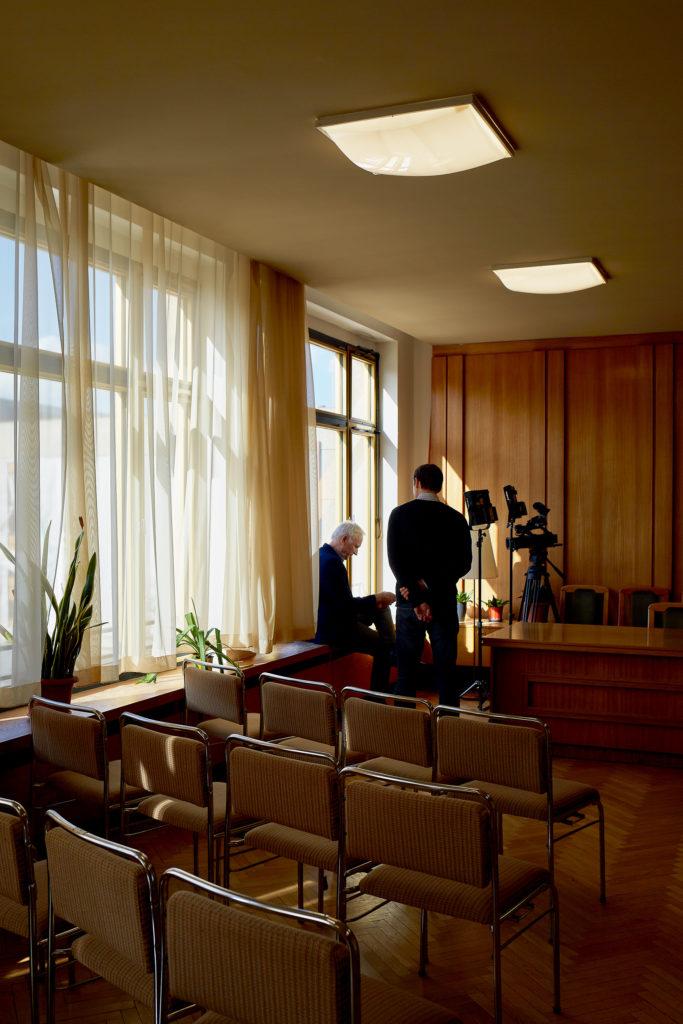 Dieter Dombrowski sitzt mit einem Handy in der Hand auf dem Fensterbrett im ehemaligen Sitzungsraum in der ehemaligen  Stasizentrale. Neben ihm steht sein Pressesprecher.