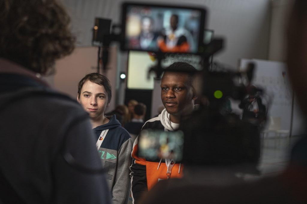 David und Ben werden von einem Kamerateam interviewt.